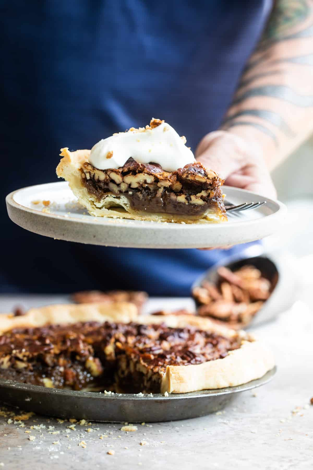 hand holding a slice of bourbon pecan pie with whipped cream