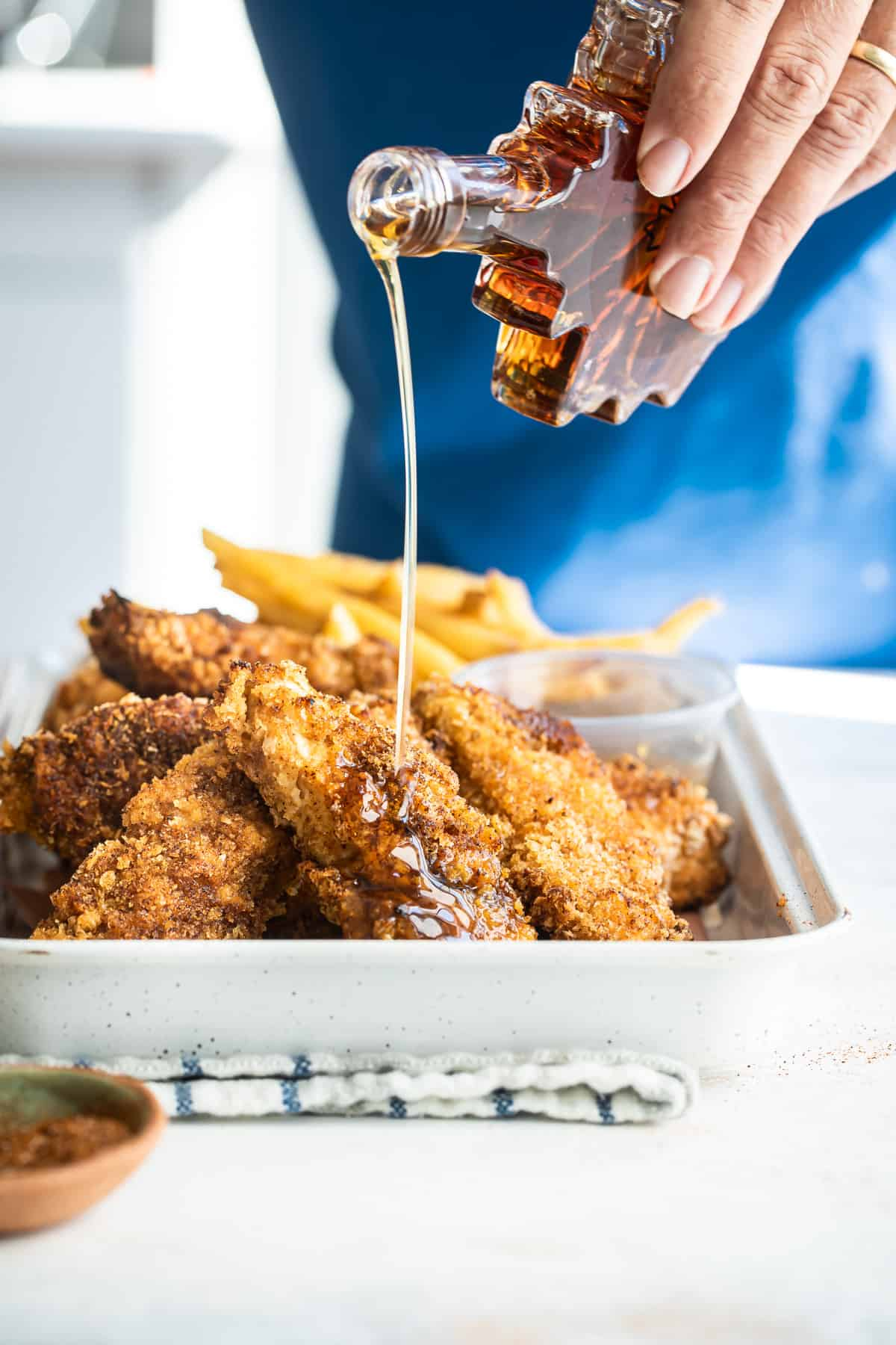 pouring maple syrup onto hot chicken tenders