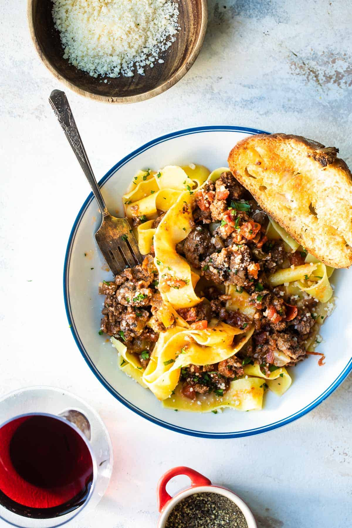 pappardelle pasta with beef ragu and crusty bread in a bowl