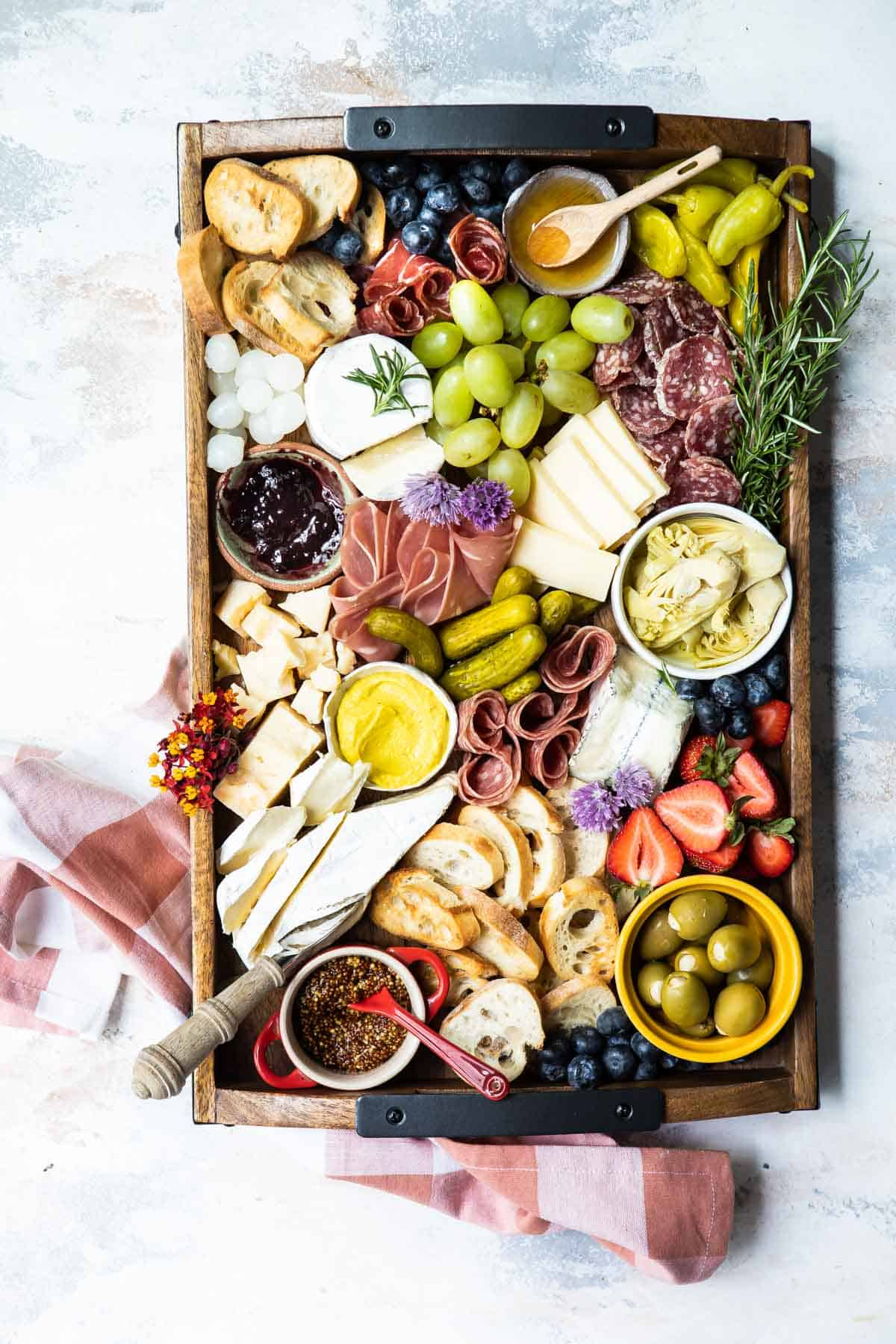 a full charcuterie platter with olives, meats, cheese and pickles