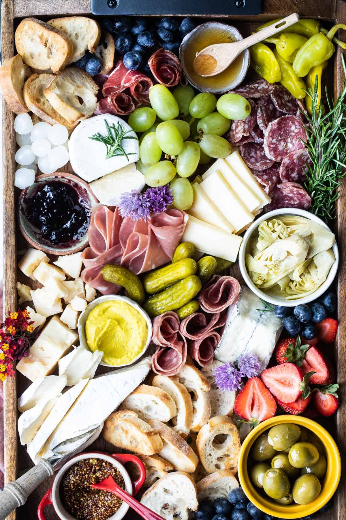 Charcuterie platter filled with meats, cheese and fresh fruits