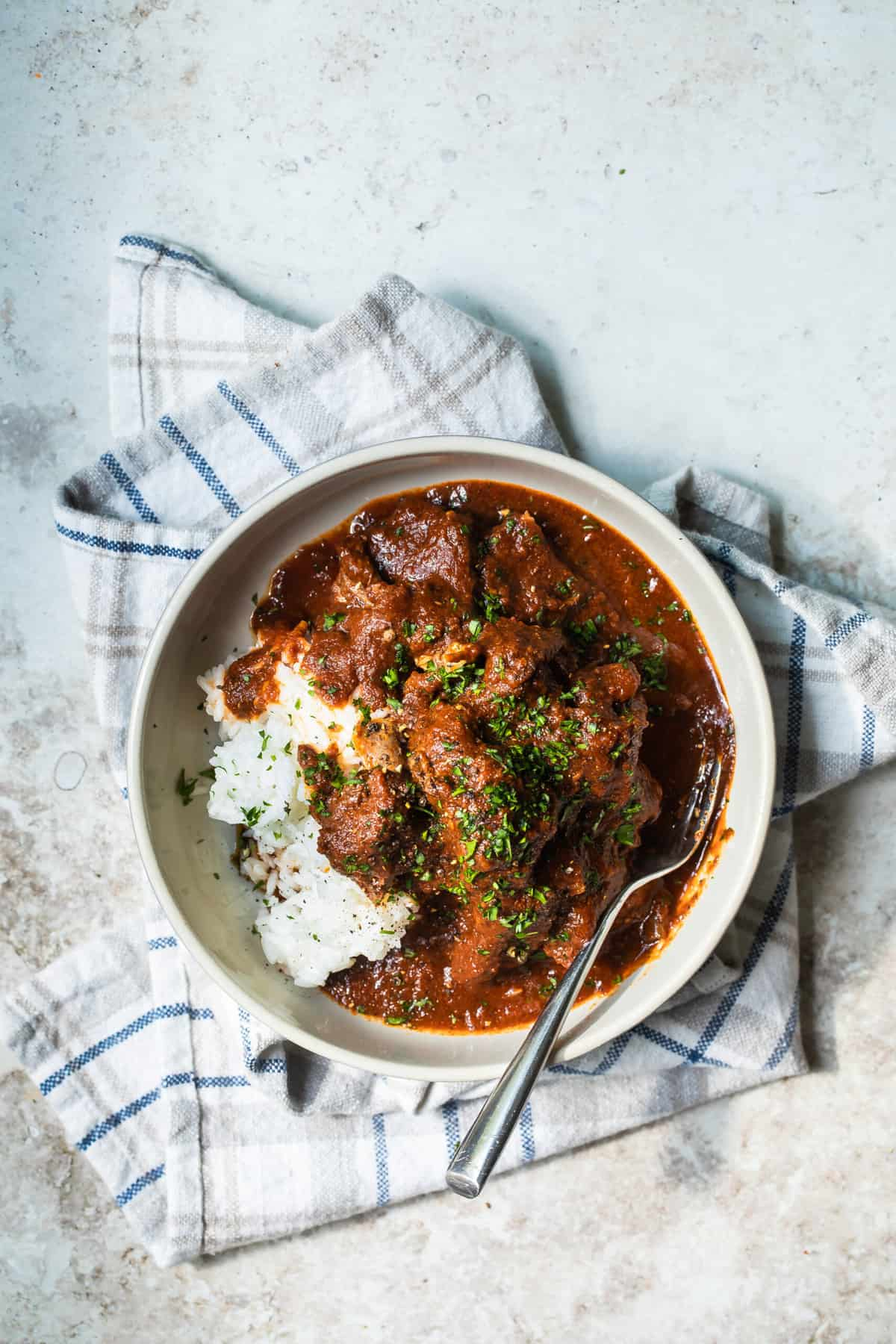lamb birria in a bowl with rice
