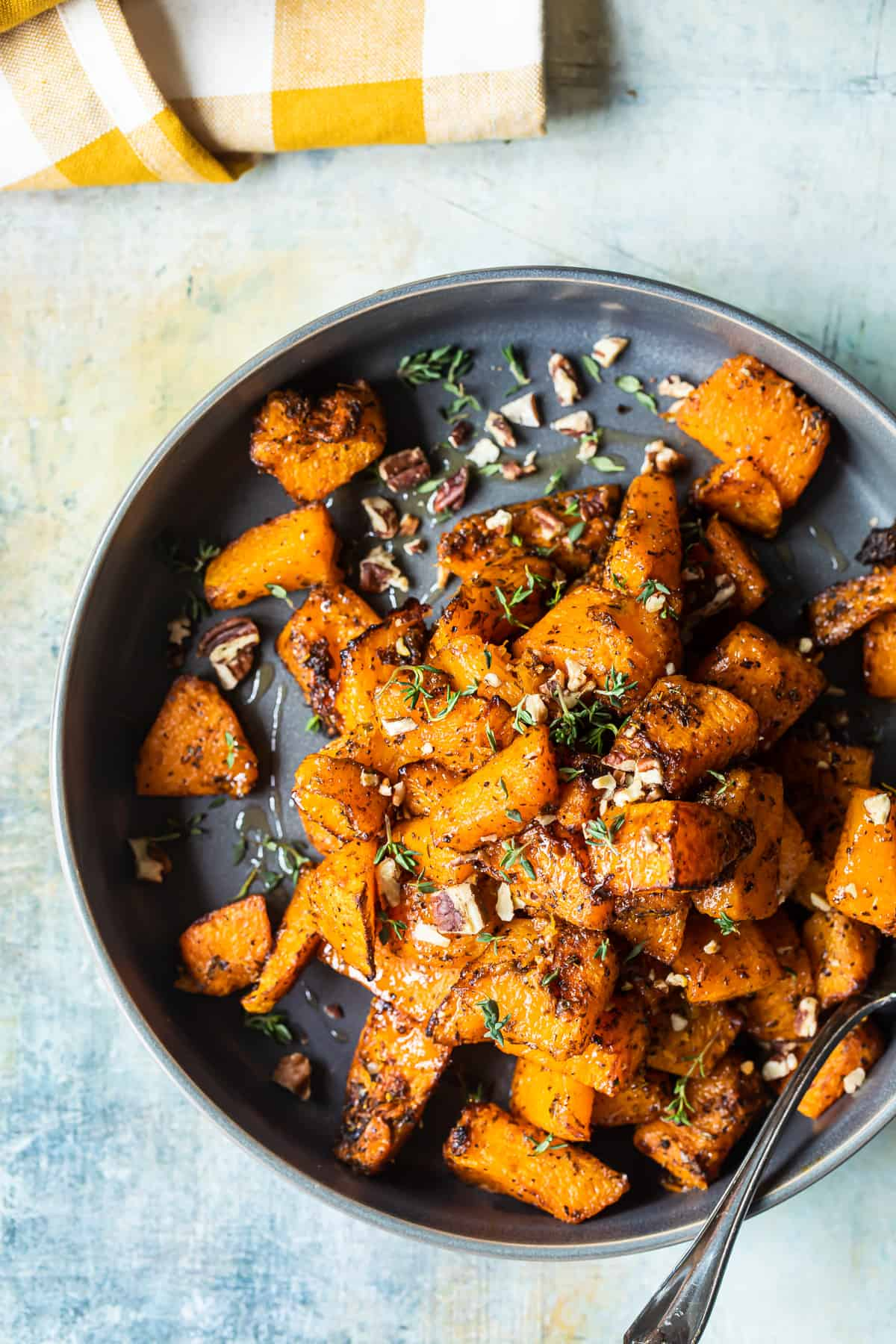 roasted butternut squash on a plate with pecans and honey