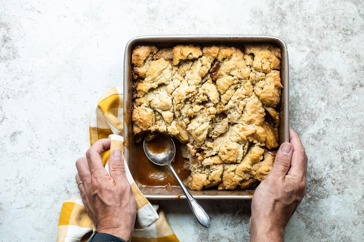 fresh baked apple cobbler with hands holding the pan